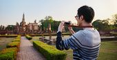 young thai male tourist taking photo with camera at sukhothai historical park thailand poster