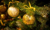 Christmas tree with silver bauble ornaments. Decorated Christmas tree closeup. Balls and illuminated poster