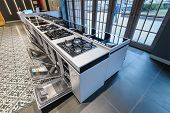 Row of dishwashers gas stoves selling in appliance retail store showroom, ovens and other home appli poster