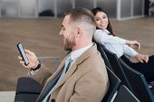 Young Businessman And Woman Waiting At Airport Lounge. Man Looking At Phone. Business Travelers Wait poster