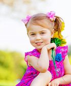 Happy baby girl playing outdoor, cute child holding fresh sunflower flowers, kid having fun in summe
