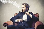 stock photo of mafia  - boss smokes cigar with a glass of champagne - JPG