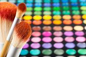 Makeup Brushes And Set Of Colorful Eye Shadows As Background
