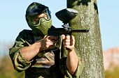 paintball player in protective uniform and mask aiming and shooting with paint marker gun outdoors