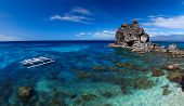 Clear tropical sea and white national boat anchored on coast of Apo island. Philippines