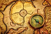 image of nautical equipment  - Vintage compass lies on an ancient map of the North Pole  - JPG