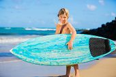 Young surfer, happy young boy at the beach with surfboard