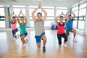 image of namaste  - Fitness class and instructor kneeling in Namaste position at exercise studio - JPG