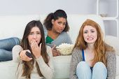pic of slumber party  - Portrait of scared young female friends with remote control and popcorn bowl on sofa at home - JPG