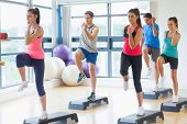 picture of step aerobics  - Full length of instructor with fitness class performing step aerobics exercise in gym - JPG