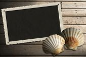 stock photo of scallop-shell  - Aged photo frame with two sea shells on beach wooden floor over summer sand - JPG