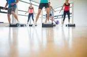 stock photo of physical exercise  - Low section of instructor with fitness class performing step aerobics exercise in gym - JPG
