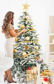 Full Length Portrait Of Young Woman Decorating Christmas Tree Wi