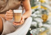 Closeup On Latte Macchiato In Hand Of Woman In Front Of Christma
