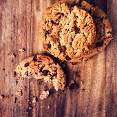 Stacked Chocolate Chip Cookies On Wooden Rustic Background In Country Style. Half Eaten Cookie With