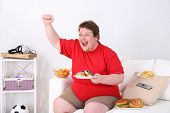image of couch potato  - Lazy overweight male sitting with fast food on couch and watching television - JPG