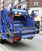 stock photo of trash truck  - Back of a big blue garbage truck in city - JPG