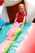 image of inflatable slide  - little girl rides with inflatable coaster in park - JPG