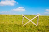 stock photo of dike  - Fencing at grassy dike and blue sky with clouds - JPG