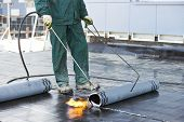 image of membrane  - Roofer installing Roofing felt with heating and melting of bitumen roll by torch on flame during roof repair - JPG