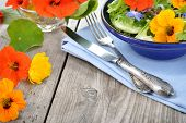stock photo of borage  - Fresh summer salad with edible flowers nasturtium borage flowers in a bowl - JPG
