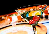pic of champagne color  - red dice in the cocktail glass in front of roulette wheel casino series - JPG