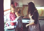 Постер, плакат: Mother with her 5 years old kids cooking holiday pie in the kitchen casual lifestyle photo series i