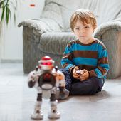 stock photo of indoor games  - Little blond boy playing with robot toy at home indoor - JPG