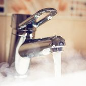 stock photo of tapping  - water tap with hot water steam - JPG