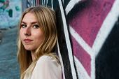 picture of nose piercing  - portrait of a young blonde girl with nose piercing and color graffiti background - JPG