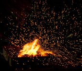 picture of charcoal  - Small BBQ on fire with burning charcoal and flying sparks - JPG