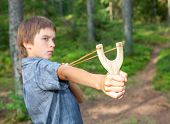 stock photo of mischief  - Boy aiming wooden slingshot outdoors - JPG