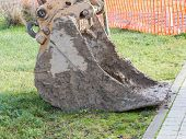 stock photo of power-shovel  - closeup of muddy excavator shovel on grass near building site - JPG