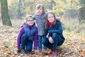 picture of three sisters  - Three sisters in the autumnal forest smiling and hugging - JPG
