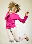 stock photo of sportive  - Portrait of a cute barefoot sportive cheerful happy girl with her hands up jumping and dancing - JPG