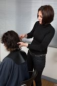 stock photo of split ends  - Stylist cutting split ends on her client at the salon - JPG