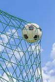 stock photo of caught  - Football caught in goal net with blue sky and white clouds - JPG