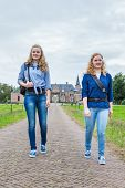 stock photo of girl walking away  - Two caucasian teenage girls hiking on road away from castle - JPG