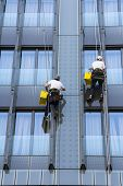 image of window washing  - Two climbers wash windows and glass facade of the skyscraper - JPG