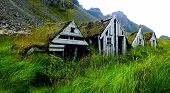 stock photo of iceland farm  - Photo of four abandoned turf houses in Iceland countryside - JPG