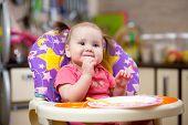 foto of spaghetti  - Pretty child toddler eating spaghetti at home - JPG
