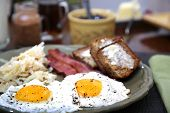 stock photo of hash  - Eggs sunny side up with hash browns bacon strips and banana bread for breakfast - JPG