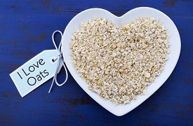 image of oats  - Plate of nutritious and healthy oat flakes in heart shaped bowl on dark blue rustic wood table with I Love Oats message tag - JPG