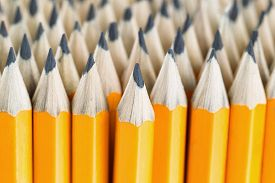 stock photo of pencils  - Close up front image of stacked pencils with focus on tip of centered pencil - JPG