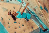 picture of climbing wall  - Beautiful sporty girl climbing on practical wall in gym bouldering - JPG