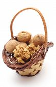 picture of walnut  - Closeup of walnut without shell and stack of walnuts in wicker basket - JPG