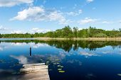 pic of bent over  - White clouds on the blue sky over blue lake with reflections with boats and boardwalk - JPG