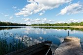 stock photo of bent over  - White clouds on the blue sky over blue lake with reflections with boats and boardwalk - JPG