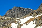 stock photo of rocky-mountains  - Picturesque view stretches over hikers on a trail going to the high rocky summit in Tatra mountains Slovakia - JPG