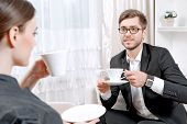 image of psychologist  - Young man wearing a black suit sitting on a couch drinking tea and talking friendly with his psychologist during therapy session - JPG